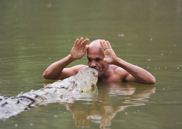 """Roger Horrocks has heard stories of men """"calling"""" wild crocodiles out of the river and a crocodile shaman who can swim and ride on the back of a giant crocodile without being eaten. Roger has experienced first hand that these ancient reptiles are possible of showing emotion and he feels a deep connection to crocodiles. He is compelled to investigate these stories and hopes to meet """"Chito"""", the crocodile shaman.Shortly after filming, Chito's beloved crocodile, Pocho died leaving this film as the only documentary of his extraordinary life.  (Photo Credit: Roger Horrocks/ NHU AFRICA)"""